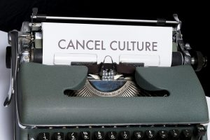 """Typewriter printing a sheet. Sheet reads """"CANCEL CULTURE"""" in sans serif capital lettering."""