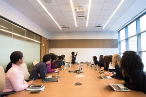 Conference meeting with woman at front pointing at whiteboard.