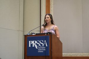 Becca Booker behind a podium with the PRSSA logo