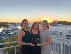 three chapter members holding the University Service Award plaque