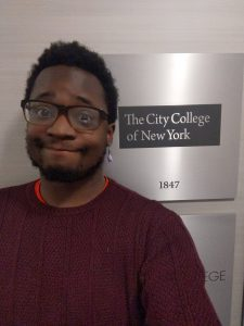 Terrell F. Merritt standing in front of a plaque with the logo of City College of New York