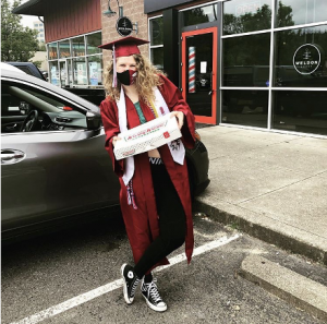 Ashleigh Panton, dressed in graduate robes and a face mask, is posing with a box of doughnuts outside of her local Krispy Kreme in Issaquah, Washington, on May 19, 2020.