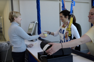 A photo of a woman using the harness system at the Go Baby Go Cafe, handing a female customer a pint of ice cream.