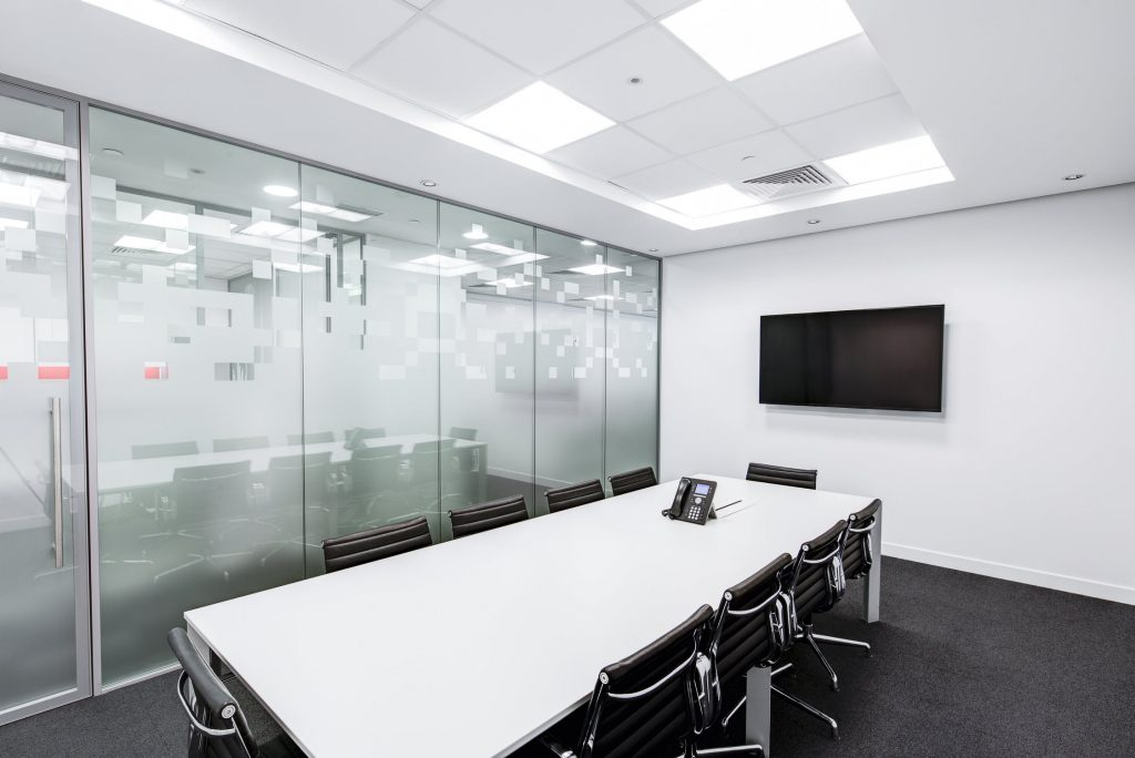 Empty office boardroom. White walls and desk. Black chairs.